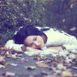 Mystic lonely angel girl lying on the ground among the fallen leaves and fe - Stock Photo
