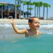 Stock Photo: Happy, two years old, baby boy enjoys swimming in sea waves. Cri