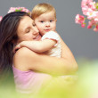 Loving mother with cute baby girl on hands among flowers — Stock Photo
