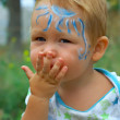 Face painted baby boy sending a blow kiss. colorful outdoor — Stock Photo