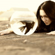 Beautiful young woman on the ground with angelfish in a bowl — Stock Photo