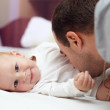 Young happy father playing  with baby. Man and baby are lying in bed. baby — Stock Photo
