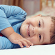 Cute smiling little boy in blue shirt lying in bed — Stock Photo
