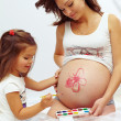 Pregnant woman with cute daughter paint mom�s belly — Stock Photo