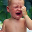 Close-up of upset little baby boy crying outdoors — Stock Photo #13554278