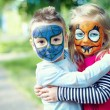 Royalty-Free Stock Photo: Two face painted little friends embracing outside