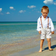 Dreamy baby boy stands in surf on sea beach — Stock Photo