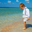 Cute baby boy walking in surf on beach — Stock Photo