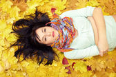 Beautiful woman lying in leaves wearing colourful scarf — Stock Photo