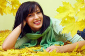 Attractive smiling brunette woman lying in yellow fallen leaves, wearing green scarf — Stock Photo