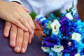 Closeup of bride and groom hands with rings and bouquet — Stock Photo