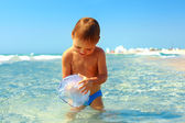 Curious baby boy catches jellyfish in the sea — Stock Photo