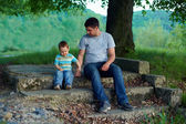 Father and son sitting on stairs under an old tree. family ties — Stock Photo