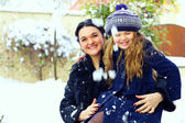 Beautiful mother and daughter smiling outdoor. winter snow — Стоковое фото