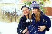 Mooie moeder en dochter glimlachend buiten. wintersneeuw — Stockfoto