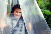 Cute little girl hiding face behind transparent tissue in summer — ストック写真