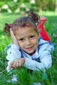 Niedliche kleine mädchen auf grünem gras liegend — Stockfoto