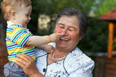 Cute grandson grabbing the nose of laughing great grandmother. f — Stock Photo