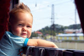 Funny little boy picking out of train window outside, while it moving. flut — Stock Photo