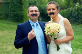 Wedding couple with funny false mustache — Stock Photo