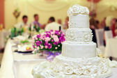 White wedding cake on restaurant interior background — Stock Photo