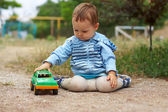 Cute baby boy playing with the toy car, sitting on the ground.countryside o — Stock Photo
