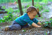 Cute baby boy digging the ground in spring forest — Stock Photo