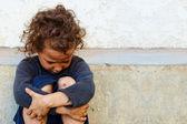 Pauvre et triste petite fille enfant assis contre le mur en béton — Photo