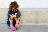 Poor, sad little child girl sitting against the concrete wall — Stock Photo