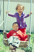 Poor but happy little gypsy siblings in swing outdoor — Stock Photo