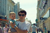Father with child on hands walking through crowd outdoor in the city — Stock Photo
