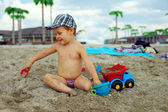 Cute baby boy playing with toys on beach — Stock Photo