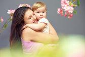 Sevgi dolu bir anne ile şirin bebek kız ellerinde çiçekler arasında — Stok fotoğraf