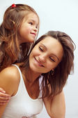 Close-up portreit of happy smiling daughter hugging beautiful mother — Stock Photo