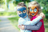 Two face painted little friends embracing outside — Stock Photo
