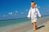 Confident baby boy goes forward in firm gait, sea beach — Stock Photo