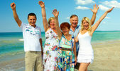 Big happy family waving hands on sea beach — Stock Photo