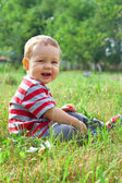 Happy smiling baby boy sitting on green summer field — Stock Photo