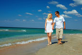 Happy couple in love walking on sea shore, vacation concept — Stock Photo
