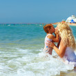 Mother and son kiss in sea water on beach — Stock Photo