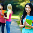 Stock Photo: Beautiful female student outdoors with a group of on the background