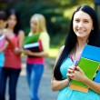 Pretty female student outdoors with a group of on the background — Stock Photo