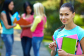 Pretty student outdoors with a group of on the background — Stock Photo
