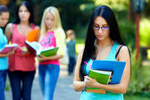 Pretty female student outdoors with a group of on the background — Стоковое фото
