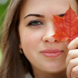 Close-up portrait of pretty woman hiding eye behind the leaf. green outdoor — Stock Photo