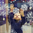 Curious baby boy catching snowflakes on shop window in city mall - Stock Photo