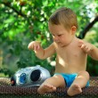 Cute baby DJ playing with retro recorder in the garden, sitting on rusty be — Stock Photo