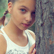 Pretty teenager girl leaning against the tree trunk — Stock Photo #13672776