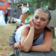 Portrait of attractive teenage girl with beautiful eyes lying on bench outd — Stock Photo