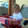 One year old baby girl sitting on bench and trying to open big red gift box — Stock Photo